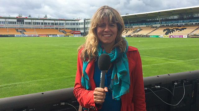 Claudia reporting beside a football pitch